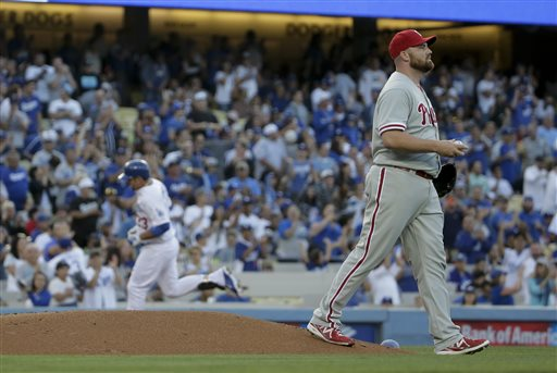 Philadelphia Phillies starting pitcher Sean O'Sullivan, right, walks away as Los Angeles Dodgers' Adrian Gonzalez rounds the bases after a home run during the first inning of a baseball game in Los Angeles, Monday, July 6, 2015. (AP Photo/Chris Carlson)